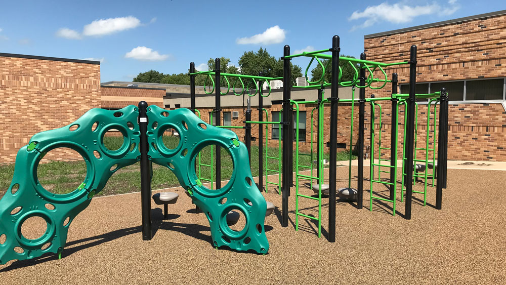 Playground climbing structures on poured-in-place rubber surfacing