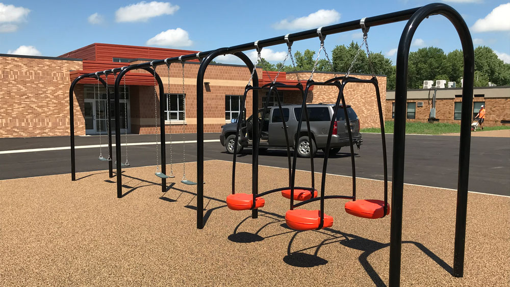 Black and red swing set for an elementary school